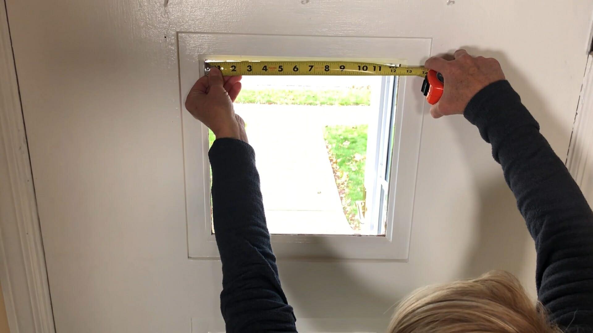 woman using a tape measure to measure window